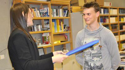 Verena Konrad überreicht Maximilian die Auszeichnung.