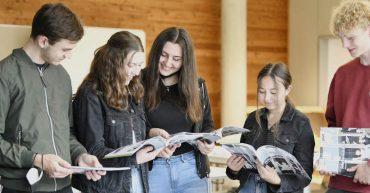 Schülerinnen und Schüler der 3. HAK blättern im neuen Jahresbericht 2021